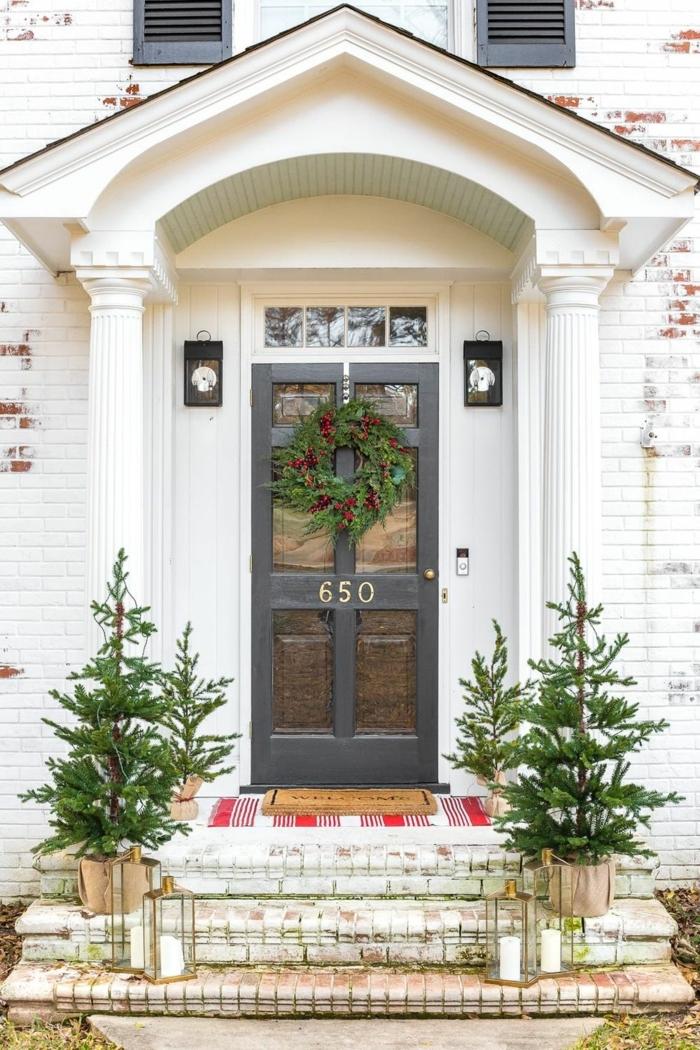 porche decorado con mucho estilo, grande corona verde en la puerta, entradas y puertas decoradas para Navidad