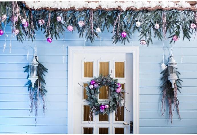 casa pintada en blanco y gris con bonita decoración navideña, adornos navideños en color lila y plateado, guirnalda de Navidad verde