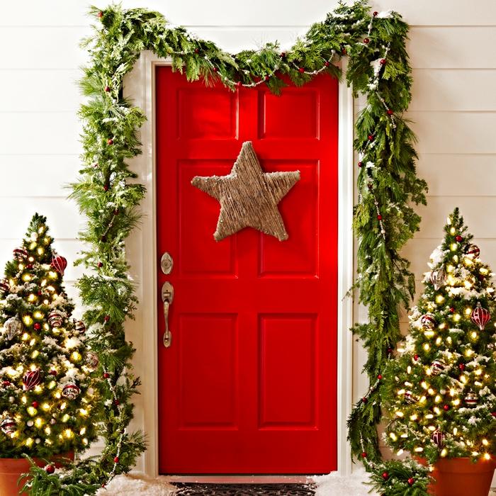 decoración clásica para Navidad, puerta pintada en rojo con una estrella navideña en dorado y gruinaldas verdes