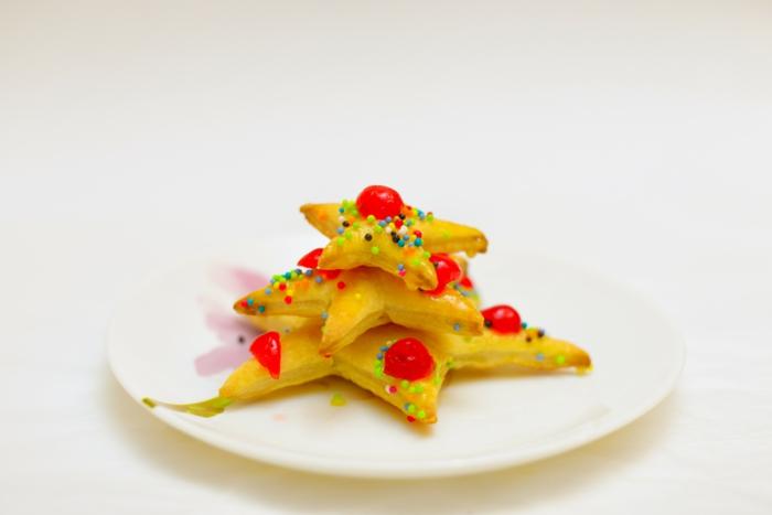 mini árbol de hojaldre con frutas azucaradas, pequeñas galletas en forma de estrella con bolas de azucar decorativas
