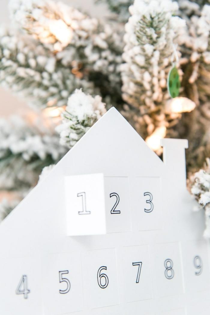 calendario de adviento casero hecho de cartón, casa de cartón con mini ventanas con números para los días del mes