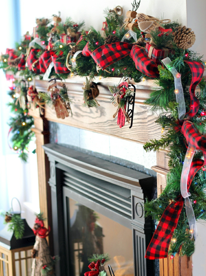 ideas acogedoras y estilosas sobre como decorar la casa en navidad, chimenea adornada con guirnalda verde con cinta decorativa