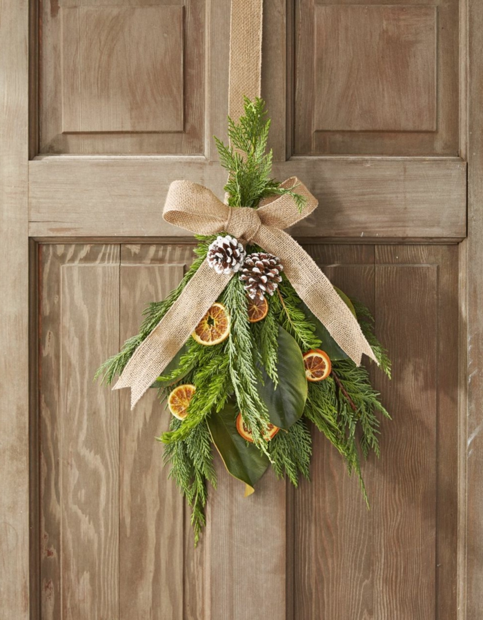 detalle decorativo en estilo rústico, ramas de pino, piñas y cinta de lino en color beige, fotos con ideas sobre como decorar la casa en navidad
