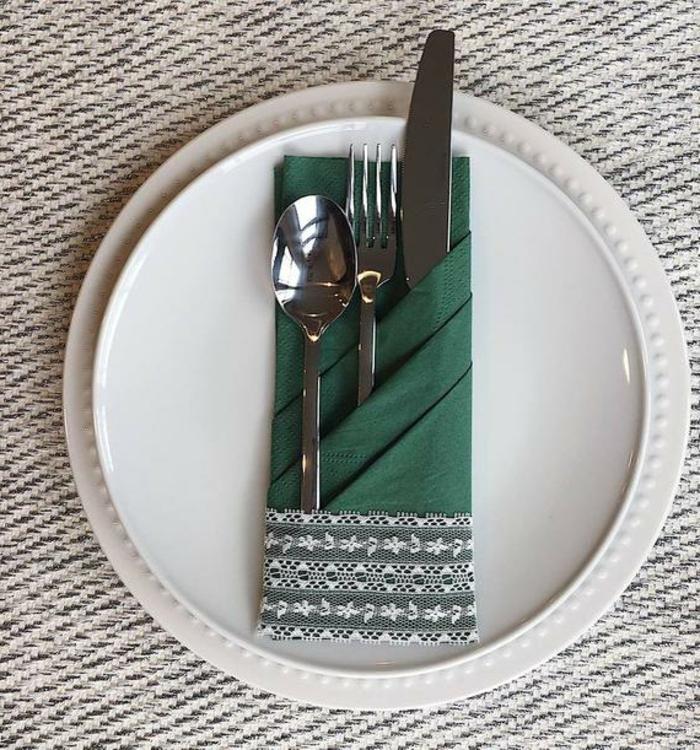 servilleta con bordado doblada con tres huecos para los cubiertos, ideas sobre como doblar servilletas elegantes