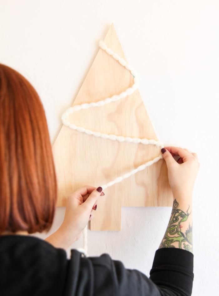 tablero de madera en forma de árbol navideño con guirnalda casera, decoración en estilo minimalista para navidad