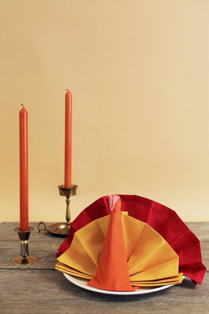 preciosas maneras de decorar la mesa en otoño, servilletas de tela en rojo, amarillo y naranja, candelabros vintage con velas color naranja