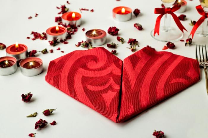 como doblar servilletas de papel para navidad y otras fiestas, servilleta de tela en color rojo doblada en forma de corazón