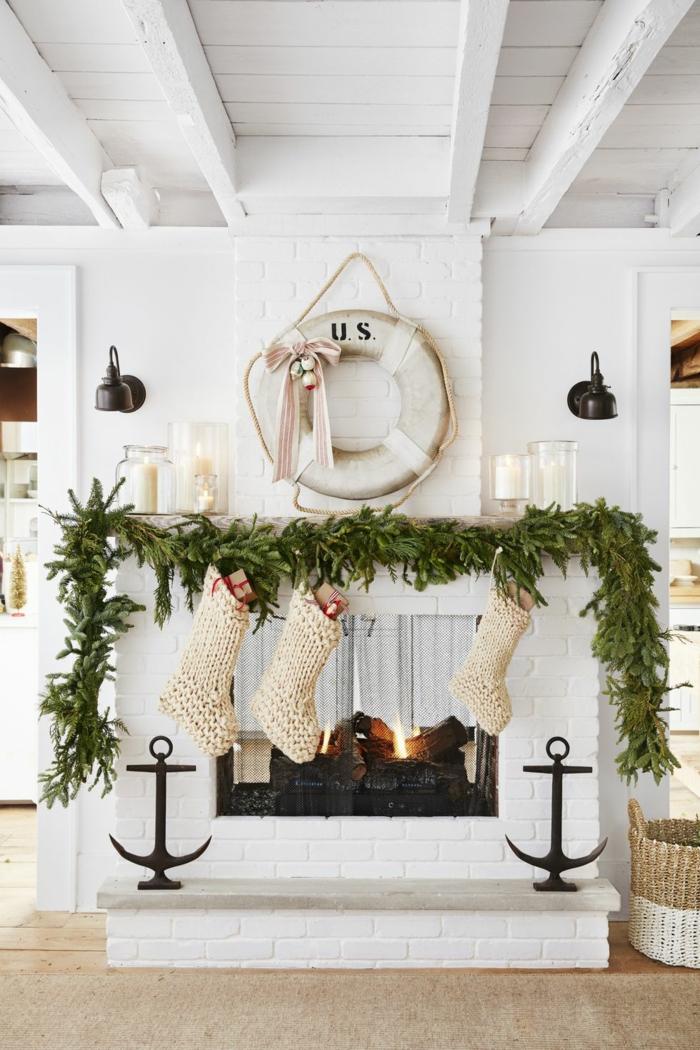 chimenea de leña decorada con guirnalda verde de pinos, tendencias en la decoración navideña 2019 2020 en fotos