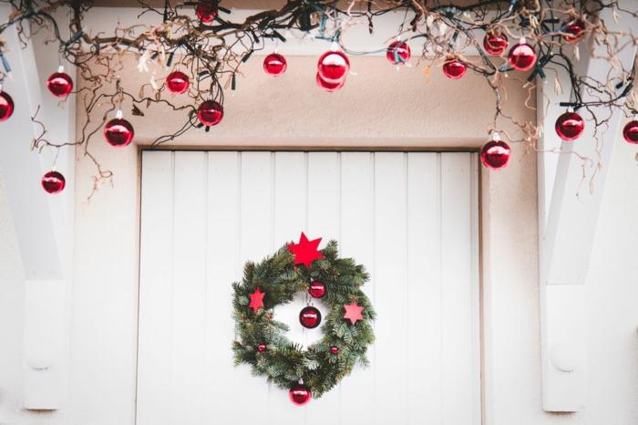 ideas decorativas simples para Navidad, corona verde con bolas rojas relucientes y estrellas de madera pintadas en rojo