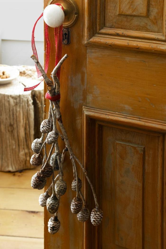 tendencias de la decoracion navideña 2019, pequeñas piñas colgadas en la puerta, decoración en estilo minimlista