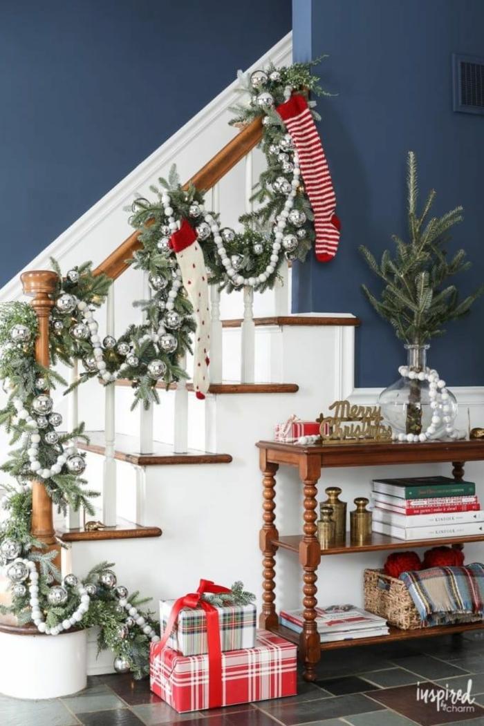 escaleras decoradas con guirnaldas verdes con adornos en color plateado, casas acogedoras decoradas para navidad