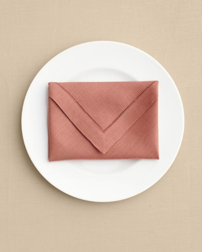 servilleta de tela doblada de una manera elegante para presentar la comida, ideas de como doblar servilletas de papel para navidad