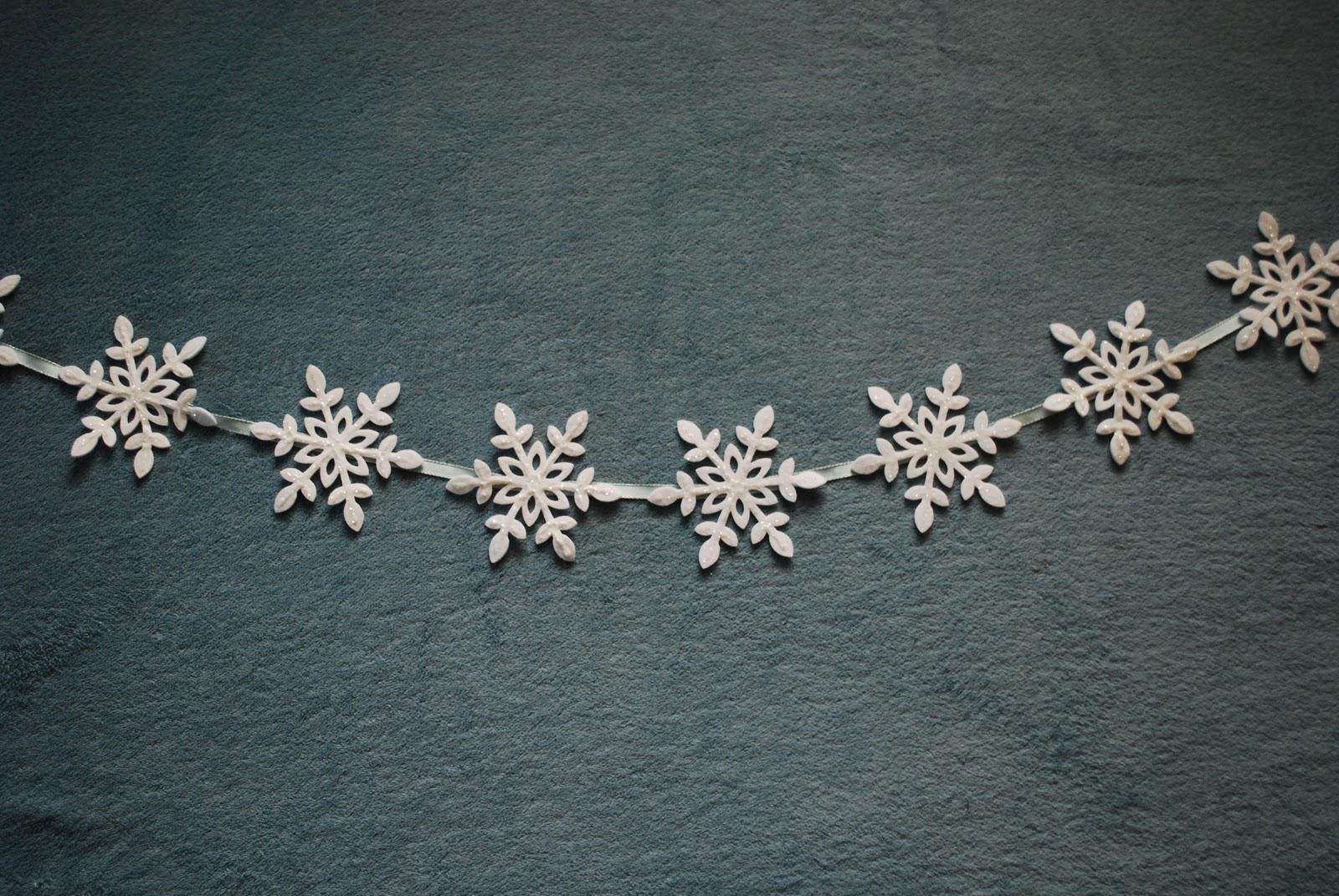 tendencias en la decoración y guirnaldas navideñas caseras, como hacer una guirnalda DIY de copos de nieve de fieltro