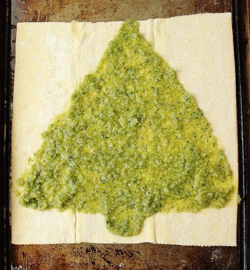 recetas de navidad aperitivos paso a paso, hoja de hojaldre con capa de pesto, pasos para hacer una empanada en forma de árbol navideñ