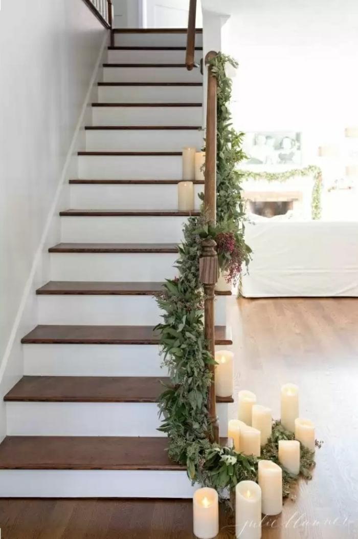 guirnalda navideñas verdes para decorar la escalera en navidad, decoración romántica con velas aromáticas blancas