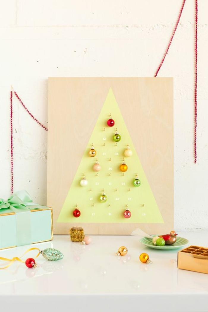 calendario de adviento DIY de un tablero de madera adornado con bolas navideñas, arbol navidad madera DIY en foto