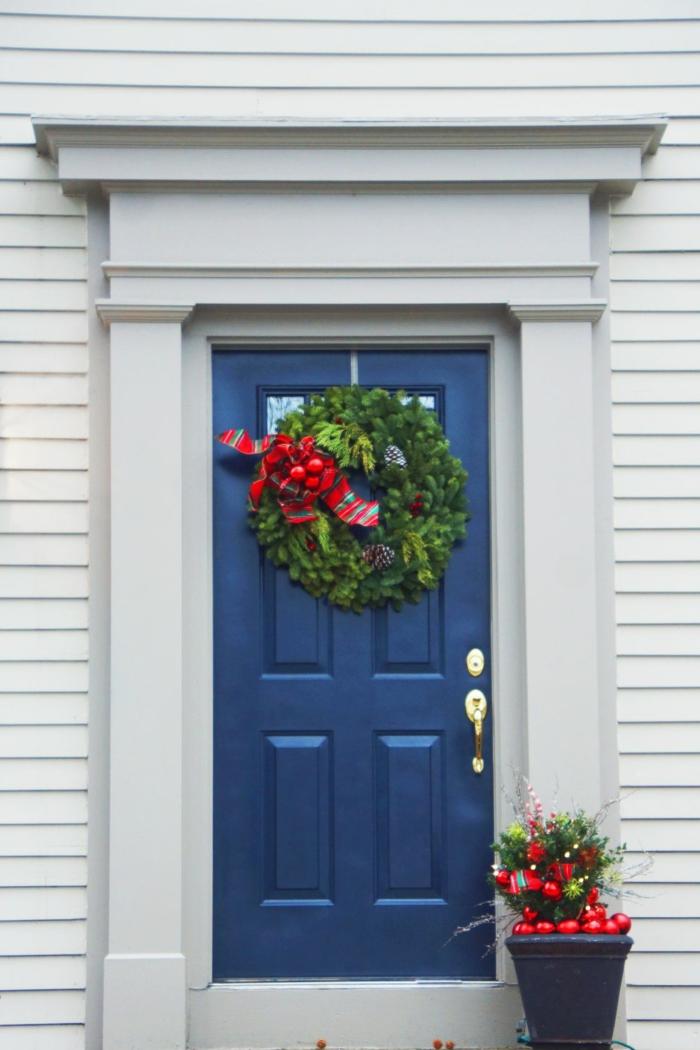 fotos de puertas decoradas de Navidad clásicas, detalles decorativos tradicionales, grande corona verde colgada a la pared