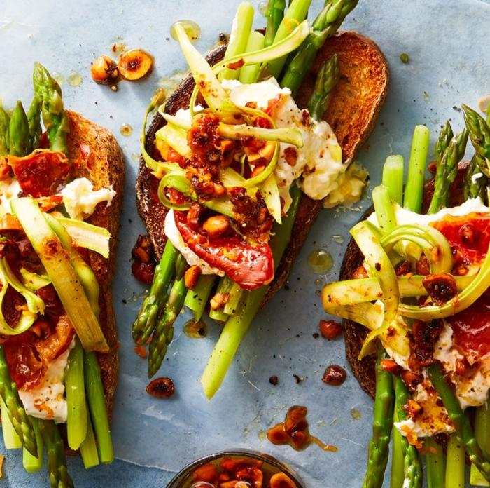 originales ideas de aperitivos para cumpleaños para compartir, tostadas con espárragos, tomates, verduras, sabores ricos