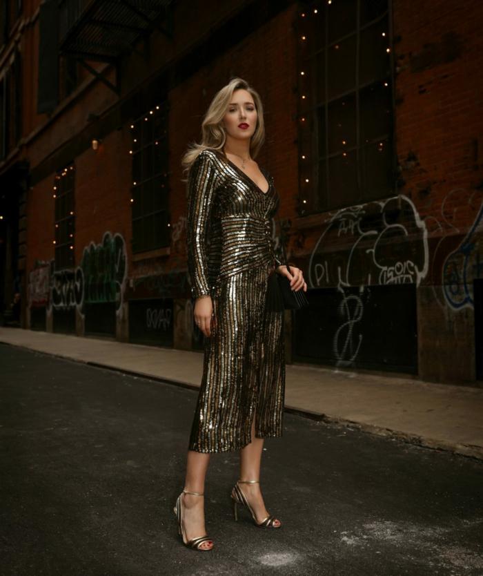 precioso vestido con brillo en dorado, tacones altos elegantes y pequeño bolso según las últimas tendencias en la moda mujer