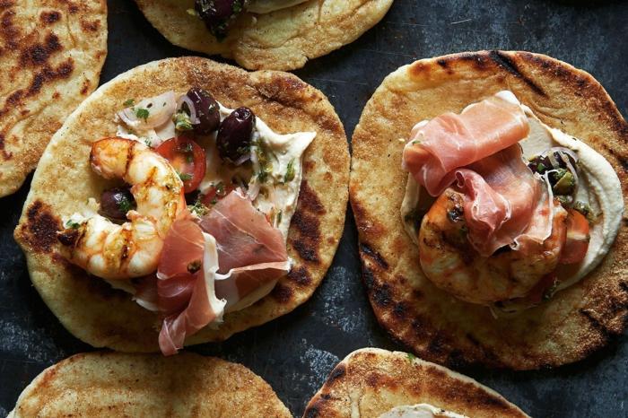 blini con antipasti, pan con hummus casero, tomates cherry, aceitunas negras y camarones, ideas de comidas para entrantes