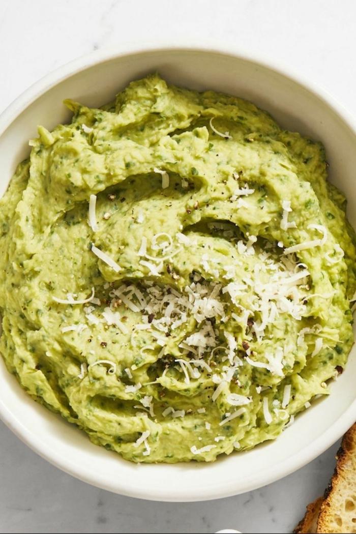 dip casero de alcachofas y espinacas con queso parmesano rallado, originales ideas de aperitivos para cumpleaños