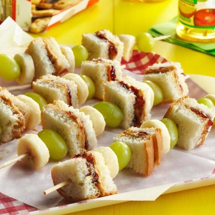 pinchos con mini bocadillos, trozos de plátano y uvas, ideas originales de merienda niños, aperitivos navidad y nochevieja
