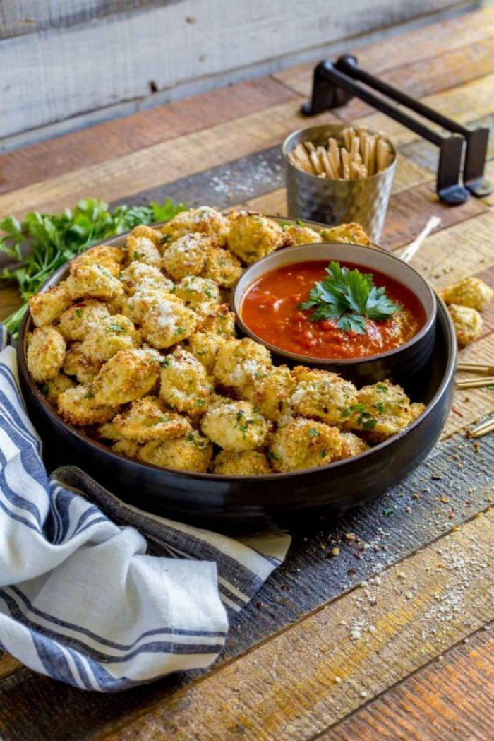 bolas de queso parmesano con salsa de tomates y perejil, ideas de entrantes para preparar para tus invitados en una fiesta casera