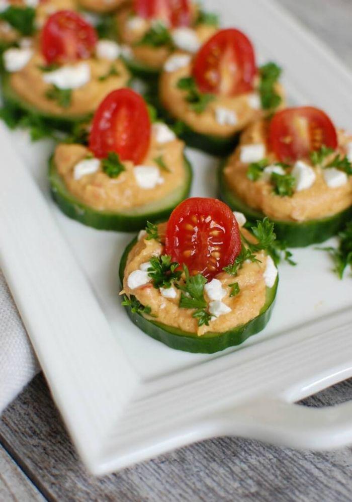 trozos de pepinos con hummus casero, queso blanco y tomates uva, bocados sabrosos y saludables para una fiesta