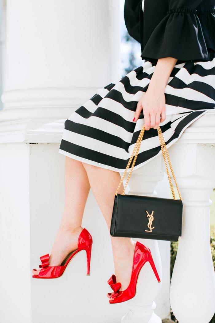 falda en rayas blanco y negro, precioso bolso negro pequeño y tacones altos en color rojo brillante, ideas de look nochevieja 2019