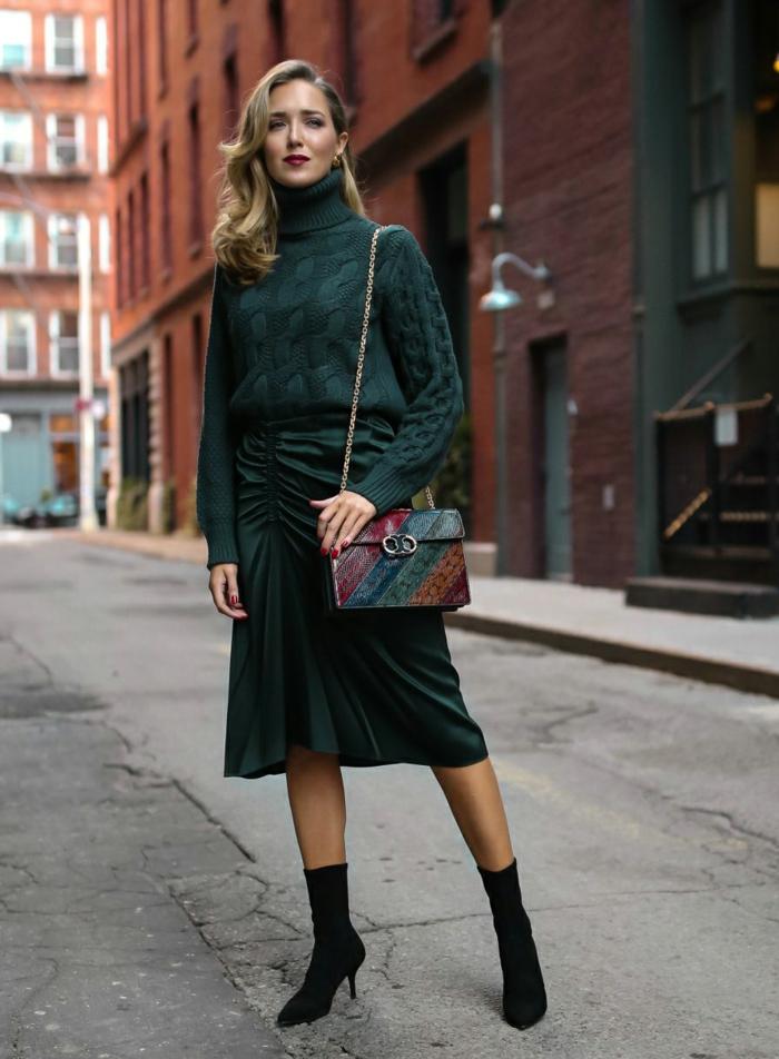 precioso atuendo en color verde oscuro, jersey elegante en negro y falda de satén con corte asimétrico, botas elegantes en tacones altos