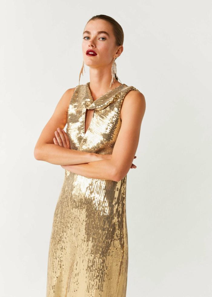 glamorosas propuestas de outfit para una fiesta fin de año, vestido en dorado con brillo, pendientes elegantes muy largos