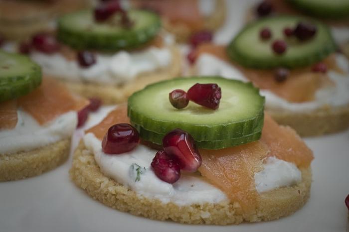 canapés frios y fáciles para preparar en casa, galleta salada con crema de queso, salmón ahumado, granada y pepinos