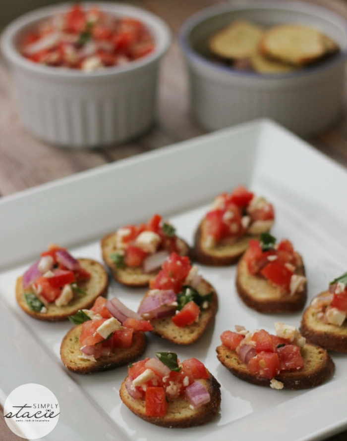 mini tostadas de pan integral, con queso blanco, tomates y cebolla roja, pinchos para navidad y canapes elegantes y ricos