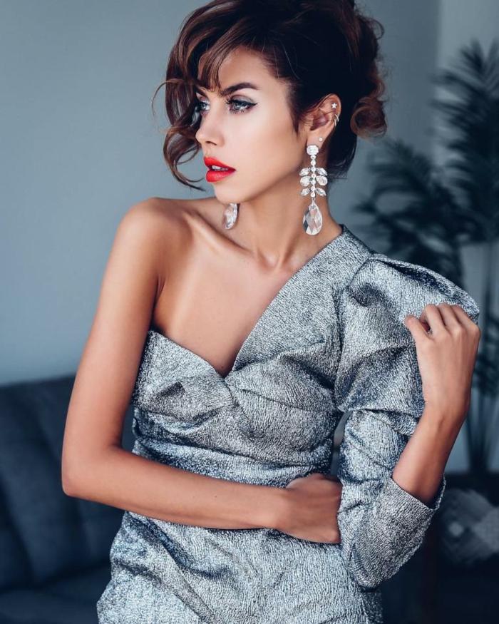 vestido elegante en color gris con brillo, corte asimétrico con manga voluminosa, pendientes largas y labios pintados en rojo