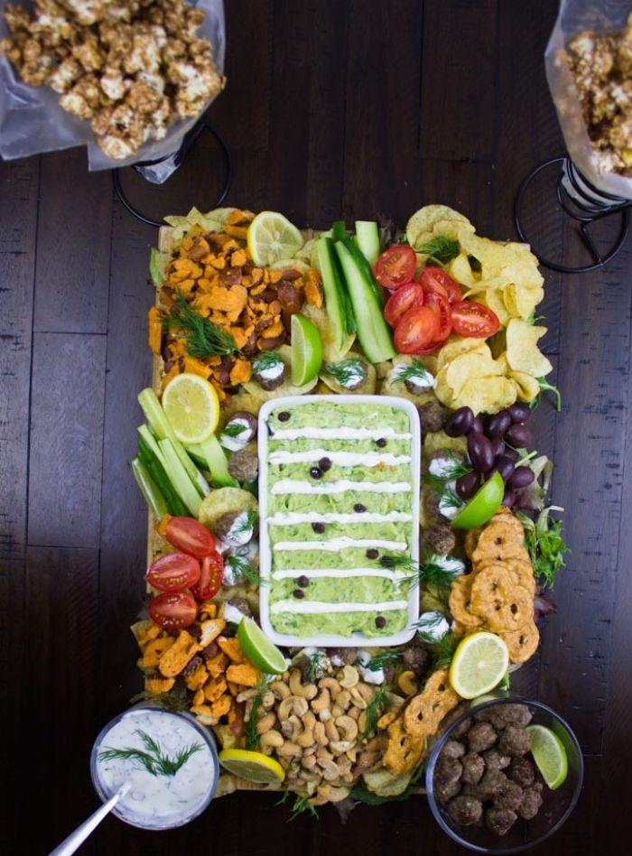 tablero con cosas para picoteo, originales ideas de comidas para preparar en casa, pepinos, anacardos, limones, papas fritas