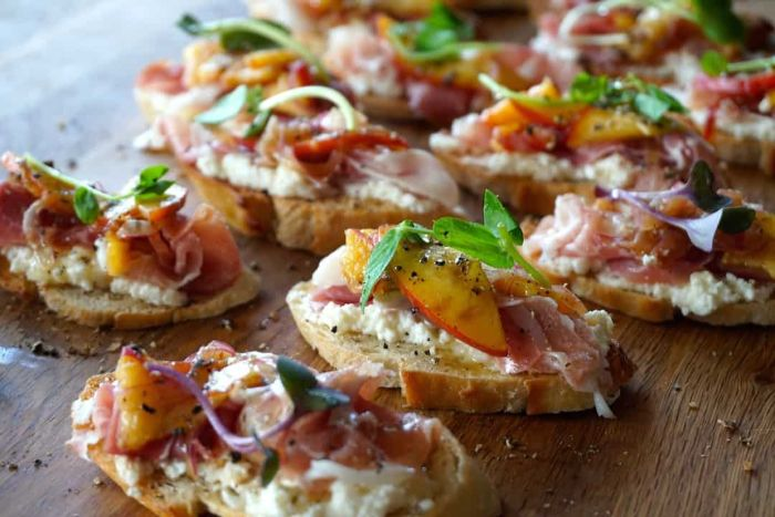 rebanadas de pan tostado con queso riccota, melocotones, hierbabuena y jamón, tostadas ricas y originales para hacer en una fiesta