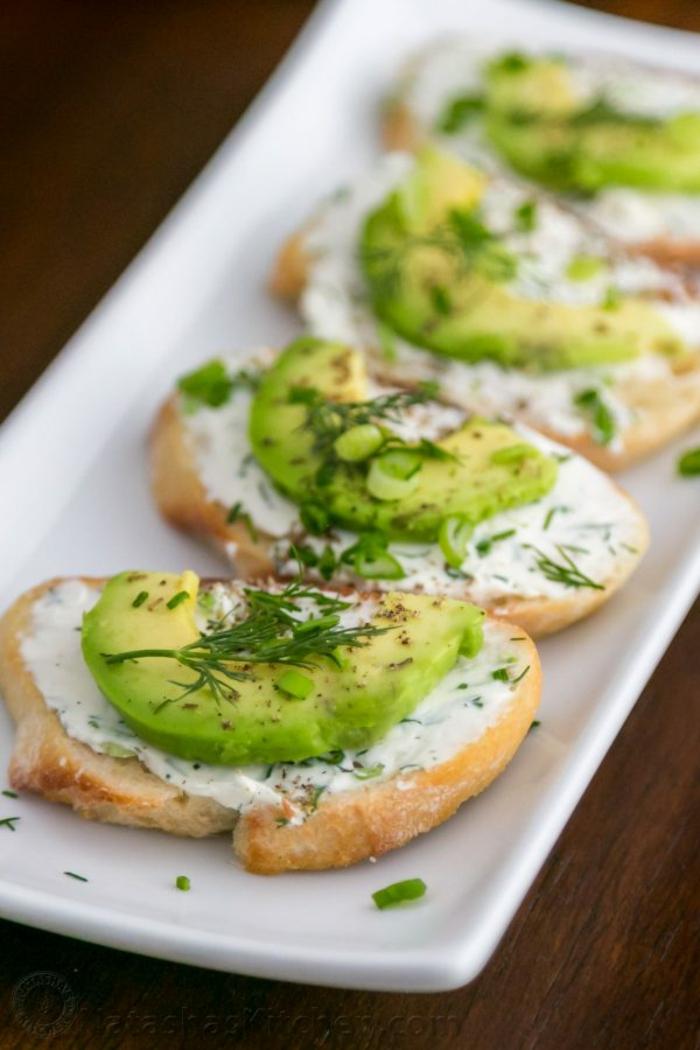 tostadas con queso crema, trozos de aguacate y eneldo, originales ideas de desayunos y meriendas, recetas de aperitivos