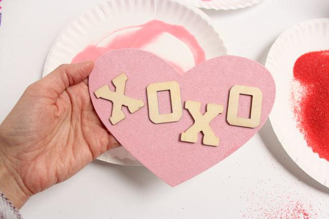 tarjeta en rosado decorada con arena en diferentes colores, postales san valentin originales y románticos, ideas en fotos