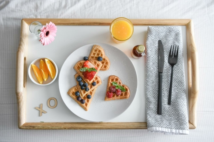 gofres en forma de corazón con arándanos y fresas frescas, jugo de naranja fresco y bonitas flores en un tablero