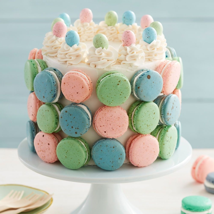 cake decoration with pastel macaroons, cake with royal icing decorated with sighs and pastel sugar eggs
