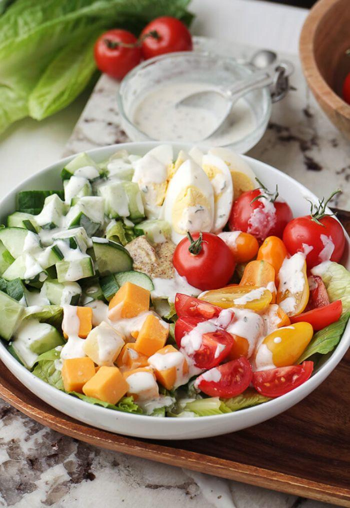 sabrosas propuestas de ensaladas keto, ensalada con pepinos, batatas, tomates uva, huevos cocidos y salsa blanca