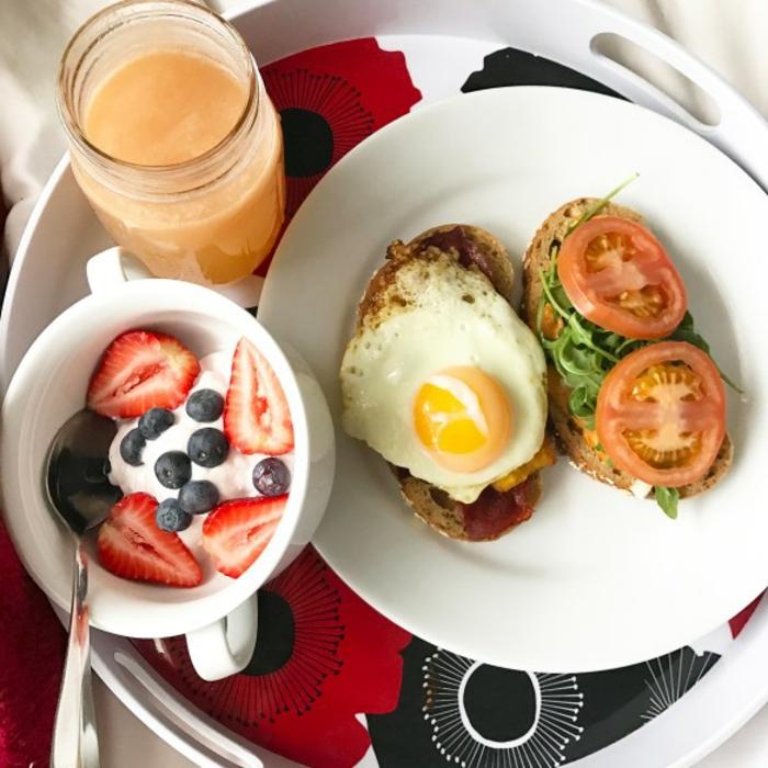 un ejemplo de desayuno nutritivo y saludable, yogur con fresas y arándanos y tostadas con huevo estrellado y verduras