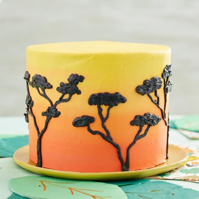 how to decorate a cake with drawings of Africa, trees drawn with black icing, cake in yellow and orange