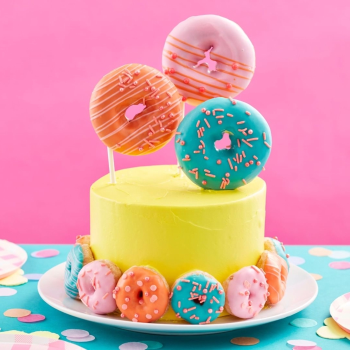 birthday cake decoration with donuts in different colors, cute birthday cake decorated with a lot of charm