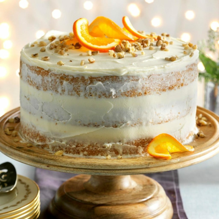 super simple decor, layered cake with white frosting, orange slices and crushed nuts, birthday cakes