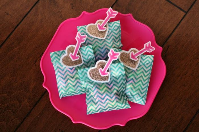 detalles para San valentin especiales, paquetes con regalos y mini tarjetas en forma de corazón y flechas de cúpido