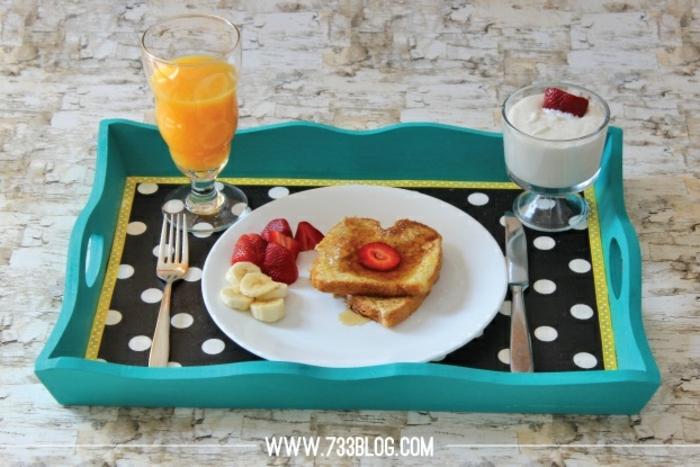 tablero con desayuno cumpleaños, taza de jugo de naranja fresco, tostadas francesas con frutas y yogur griego con fresas