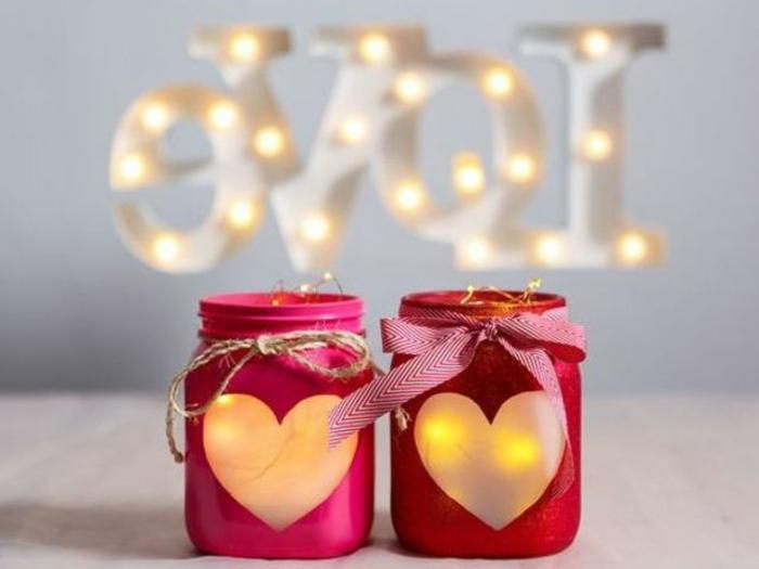 frascos decorativos con cintas y corazones con velas aromaticas, pequeños elementos decorativos para usar como centro de mesa