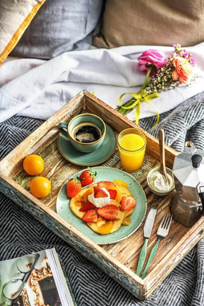 desayuno romántico en un tablero de madera en estilo rústico, crepes con crema espesa y fresas frescas, ideas de comdias