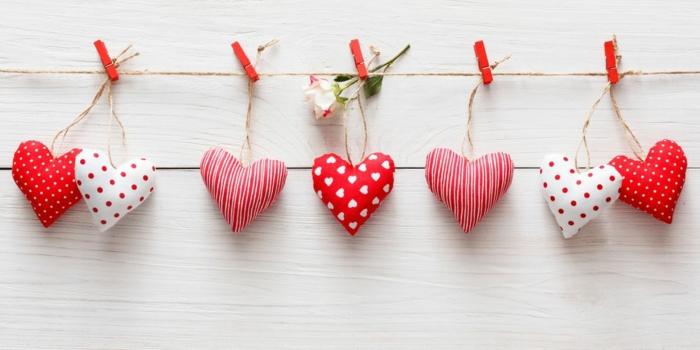pequeños detalles en forma de corazon colgados a una cuerda, bonitos corazones pequeños en blanco y rojo para decorar la pared